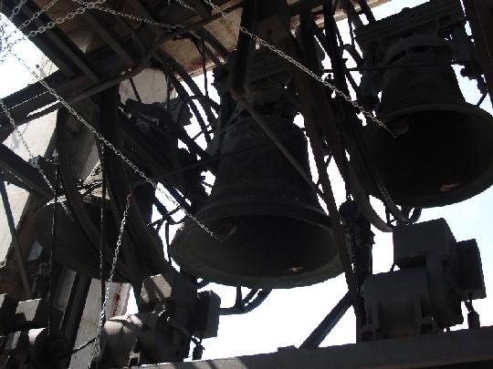Nella foto: Le campane numero 4, 6 e 3 (da sinistra a destra), collegate alla tastiera dal sistema di catenelle, secondo il sistema di suono genovese. Notare la catena che blocca il movimenco della 6a campana. Foto di Sebastian Prestini.