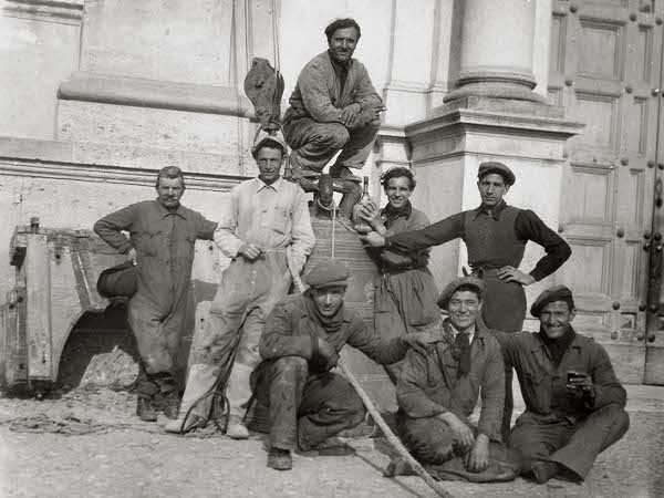 Immagine del 1943 ritraente un gruppo di operai che ha appena calato le campane maggiori della Prepositurale Plebana. Secondo il decreto di Mussolini, i bronzi di grandi dimensioni di ogni campanile vennero calate per essere convertite in cannoni da guerra.